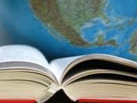 Photo d'un livre ouvert devant un globe terrestre
